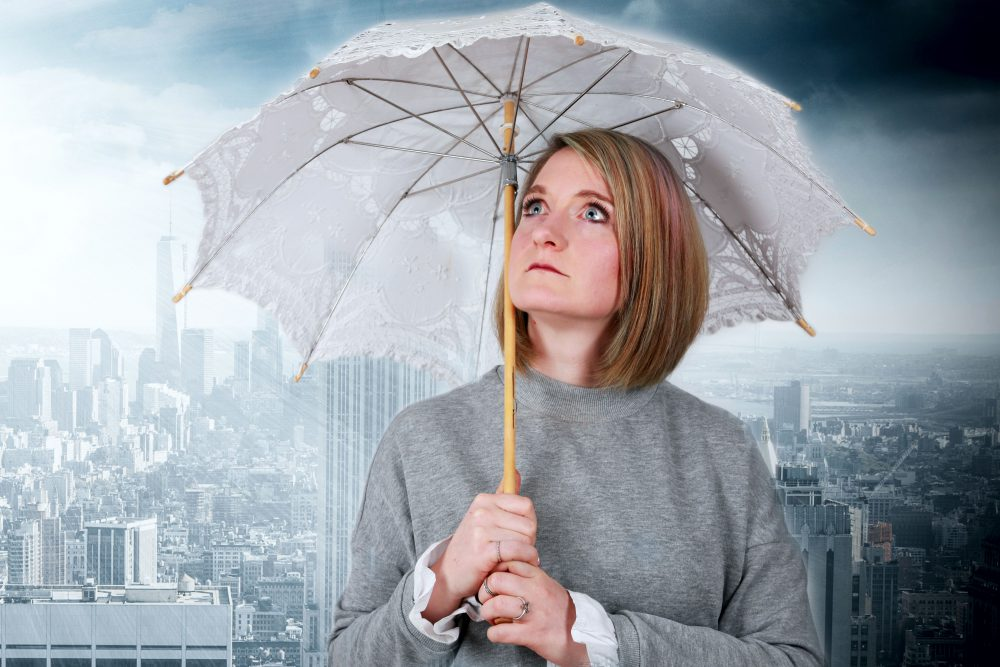 Frau hält Regenschirm vor dunkler Kulisse einer Stadt