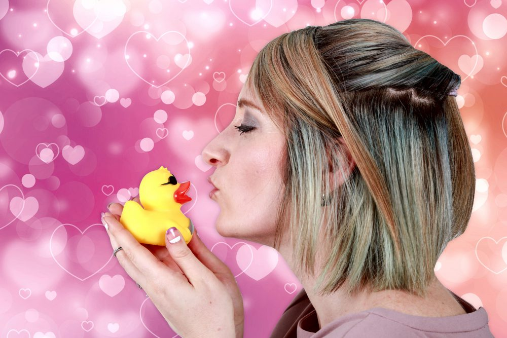 Frau küsst Quietscheentchen