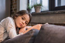 Mädchen nachdenklich auf Sofa